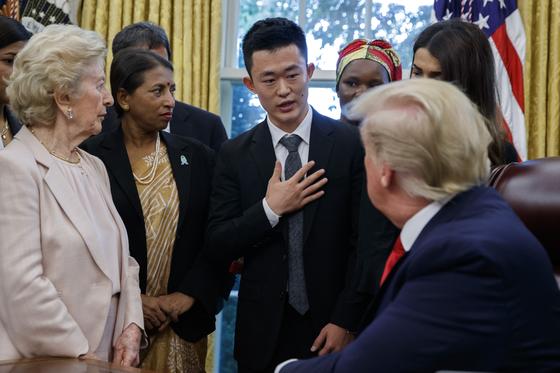 도널드 트럼프 미 대통령이 17일(현지시간) 백악관 집무실에서 탈북자 주일룡(가운데)씨의 얘기를 듣고 있다. 트럼프 대통령은 이날 주씨 등 전세계 각지에서 종교 탄압을 당했던 이들을 초청해 만났다.[AP=연합뉴스]