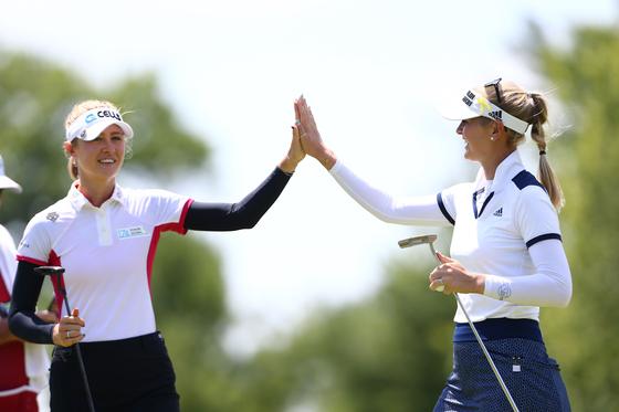넬리 코다(왼쪽)와 제시카 코다가 18일 열린 LPGA 투어 다우 그레이트 레이크스 베이 인비테이셔널 첫날 8번 홀에서 파 퍼트가 들어간 뒤 손을 맞잡고 있다. [AFP=연합뉴스]