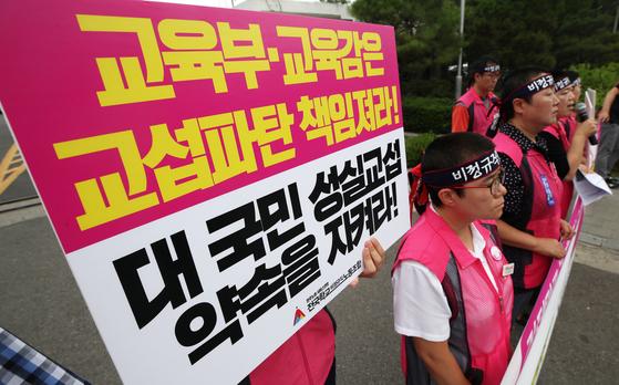 학교비정규직노조 조합원들이 18일 서울 종로구 서울시교육청 앞에서 기자회견을 열고 제2차 총파업을 선포하고 있다. [뉴스1]