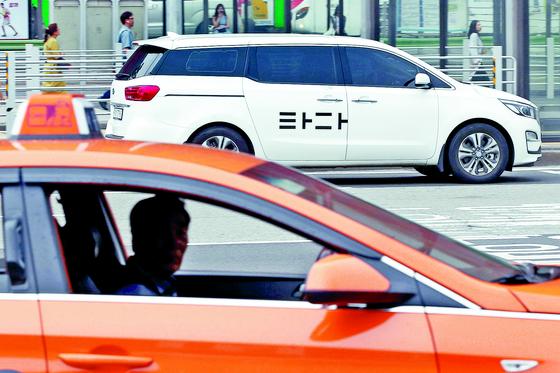 17일 오후 서울 도심에서 운행 중인 택시(아래)와 '타다' 차량. 정부는 택시기사 자격 보유자들에 한해 타다 등 승차공유 차량을 운행할 수 있도록 제도를 개편할 계획이다. [뉴스1]