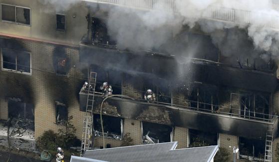 18일 오전 10시 35분께 방화로 불이 난 교토시 후시미(伏見)구 모모야마(桃山)의 애니메이션 제작회사 '교토 애니메이션' 스튜디오 건물에서 소방관들이 화재를 수습하고 있다. [교도=연합뉴스]