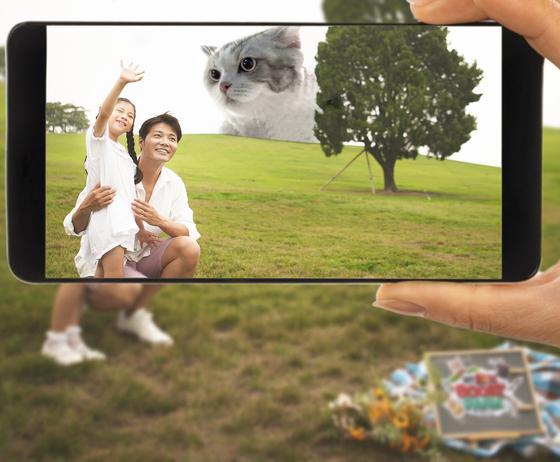 서울 올림픽공원에서 가족 여행객이 증강현실(AR) 기술로 구현한 '자이언트 캣(거대 고양이)'을 즐기는 모습. [사진 SK텔레콤]