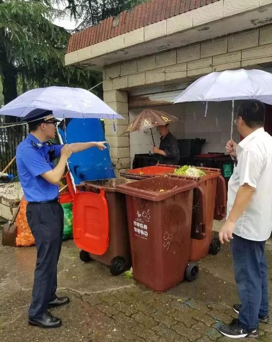 부서진 우산으로 비를 피하면서 분리수거 단속을 진행하는 감찰 요원. [출처 新民晚报]