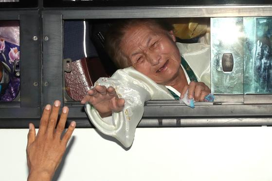 제21차 이산가족 상봉행사 2회차 마지막날인 26일 북한 금강산호텔에서 열린 작별상봉 및 공동중식을 마치고 버스에 오른 북측 가족들이 남측 가족들과 헤어지며 눈물을 흘리고 있다. [뉴스1]