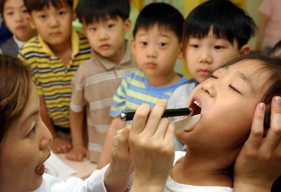 어린이 치과 치료에서는 아이가 신뢰감을 가지고 편안하게 느끼도록 하는 것이 중요하다. 치과에서의 나쁜 기억은 이후 두려움과 불안으로 나타나게 되므로, 아이의 성격과 경험, 보호자의 성격과 처한 환경 등에 맞는 적절한 치료가 필요하다. [중앙포토]