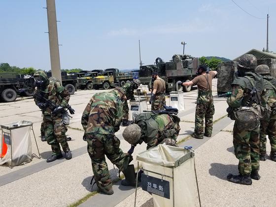 화생방 방호복과 가스 마스크 차림의 한국군과 미군이 화생방 보호복을 제독하는 훈련을 하고 있다. [사진 미 제2 보병사단]