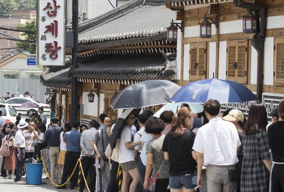 복날을 맞아 서울 종로구의 한 삼계탕 식당 앞에 줄지어 서 있는 손님들. [연합뉴스]