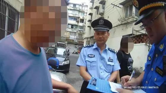 양푸취(杨浦区)에서 발생한 첫 번째 벌금 부과자가 경찰에게 고지서를 받고 있다. [출처 新民晚报]