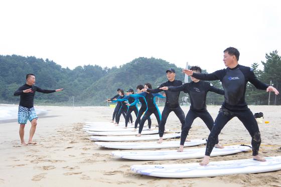 지난 15일 오후 강원도 양양의 한 해변에서 서핑 교육을 받는 공무원들. [사진 양양군]