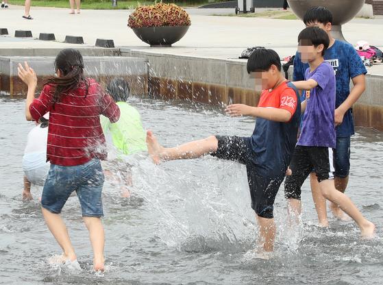 태풍이 북상하는 속에서도 서울과 춘천 등지에는 19일 밤 열대야가 나타났다. 서울을 비롯한 경기 및 강원지역에 폭염주의보가 발령된 19일 서울 영등포구 여의도물빛광장을 찾은 학생들이 물놀이를 즐기고 있다. [연합뉴스]