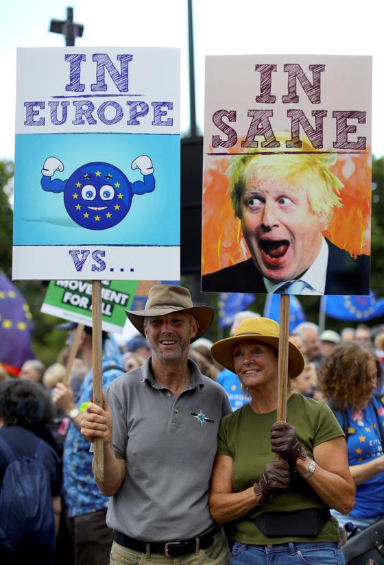 브렉시트를 반대하는 시민들이 20일 영국 런던에서 보리스 존슨 전 외무장관을 패러디 한 손팻말을 들어보이고 있다. [ AP=연합뉴스]