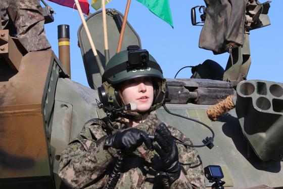 13일 혹한기 훈련에 참여한 말리나 인턴기자가 조종석에 들어가며 전차병 헬멧 마이크를 전차에 연결하고 있다. [박용한]