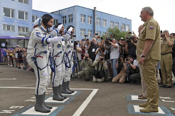 20일 우주인들이 소유즈 우주선탑승에 앞서 러시아 우주기지 대장(오른쪽)에게 경례를 하고 있다.[AP=연합뉴스]