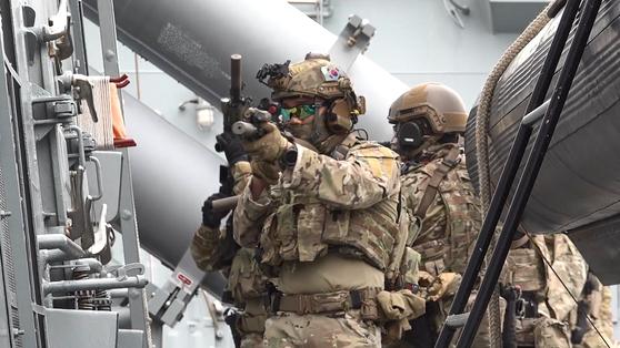 대원들이 전방을 주시하며 이동하면서 격실문과 주변을 경계한다. 무전기로 대화하거나 몸에 손을 올리며 교감한다. [영상캡처=강대석 기자]