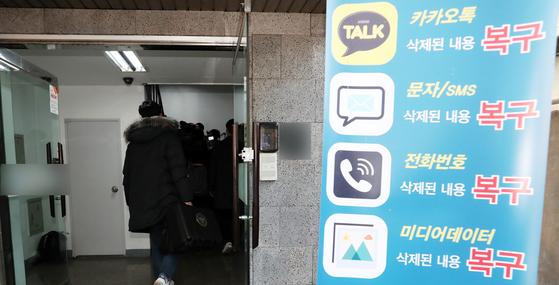 불법촬영물 유포 혐의를 받고 있는 가수 정준영씨가 과거 휴대폰 수리를 맡겼던 사설 수리업체에 대해 압수수색을 진행 중인 경찰이 13일 오후 서울 강남구 휴대폰 사설수리업체로 가방을 들고 들어가고 있다. 2019.3.13/뉴스1