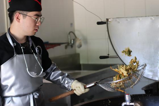 조리병은 높은 계급이 더 힘들고 어려운 임무를 맡는다. 특히 기름 온도가 180℃가 넘어서는 위험한 튀김 요리는 선임병들이 맡는다. 분대장 정민구 상병이 능숙한 솜씨로 야채튀김을 만들고 있다. [사진 박용한]