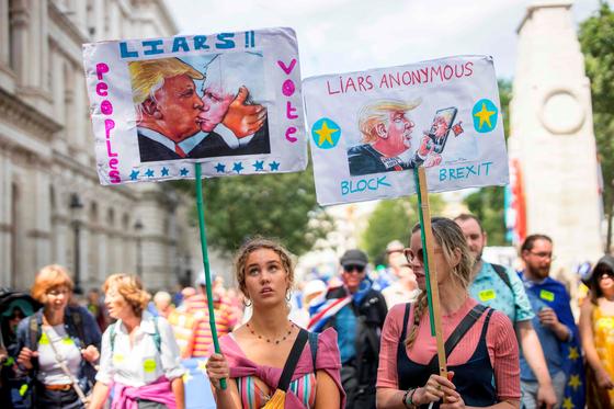 브렉시트를 반대하는 시민들이 20일 런던에서 보리스 존슨을 비난하는 손팻말을 들어어보이고 있다. [AFP=연합뉴스]