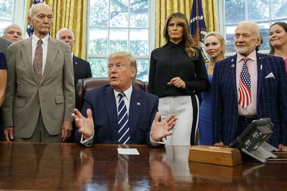 """도널드 트럼프 미국 대통령이 19일 백악관에서 아폴로 11호 달 착륙 50주년 기념 행사에 마이클 콜린스(왼쪽), 버즈 올드린(멜라니아 건너 오른쪽) 당시 우주인들과 함께 했다. 일본의 한국에 대한 반도체 소재 수출규제 발표 19일 만인 이날 트럼프 대통령은 """"문재인 대통령에게 한일 무역갈등 관여를 요청받고 '내가 얼마나 많은 일에 관여해야 하나'라고 했다""""며 """"양국이 모두 원한다면 개입할 수 있을 것""""이라고 말했다.[AP=연합뉴스]"""