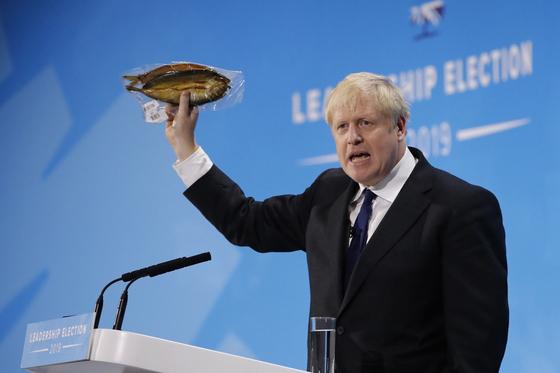 보리스 존슨 전 외무장관이 17 일(현지시간) 런던 보수당 지도부 선거전에서 비닐 포장된 청어를 들어보이며 연설하고 있다. [AFP=연합뉴스]