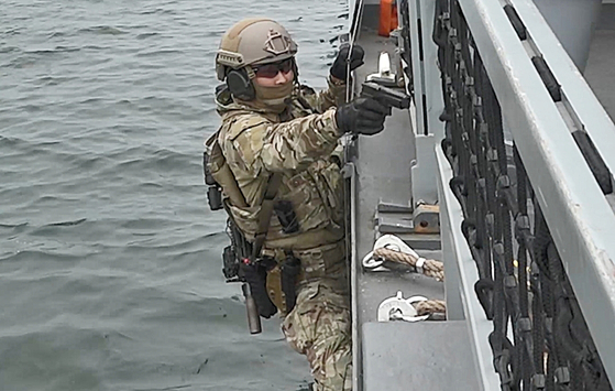 줄사다리로 선박에 가장 먼저 오른 대원이 권총으로 주변을 경계하고 있다. [영상캡처=정수경 기자]