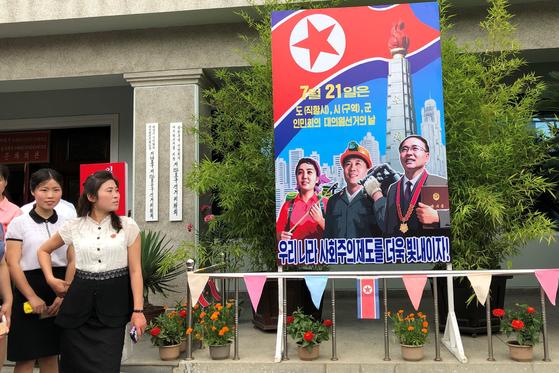 북한 여성들이 21일 지방인민회의 대의원 선거에 투표후 선거장 밖에 걸린 선서 포스터를 살펴 보고 있다. [TASS=연합뉴스]
