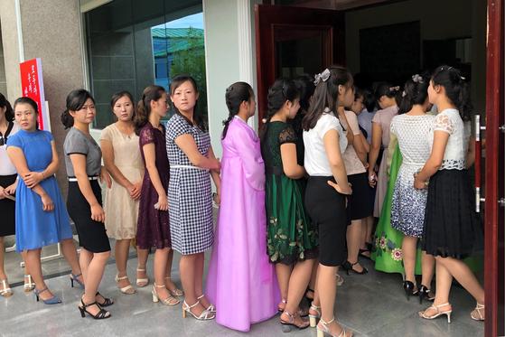 북한 여성들이 21일 지방인민회의 대의원에 투표를 하기 위해 선거장 밖에서 줄지어 서 있다. [TASS=연합뉴스]