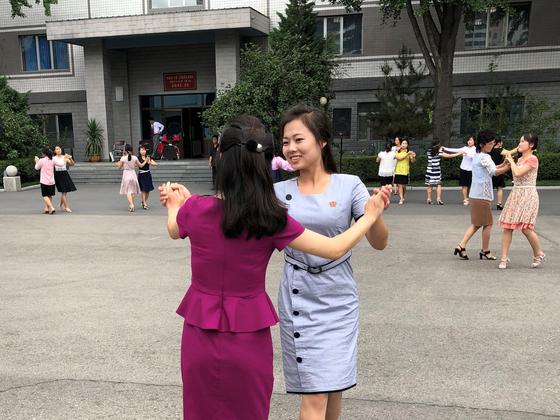 평양시민들이 21일  지방인민회의 대의원에 투표를 마친 뒤 선거장 밖에서 춤을 추고 있다. [AP=연합뉴스]