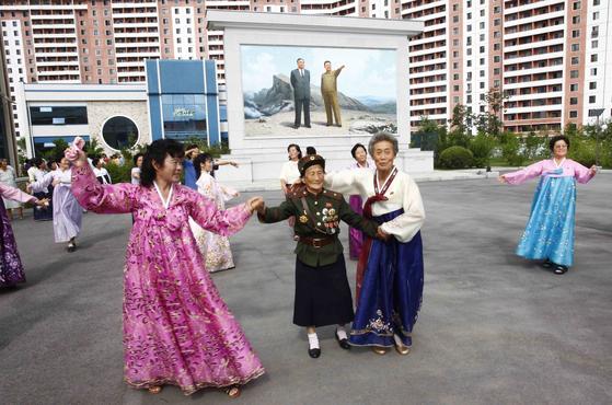 평양시민들이 21일  지방인민회의 대의원에 투표를 마친 뒤 선거장 밖에서 노래를 부르며 춤을 추고 있다. [AP=연합뉴스]