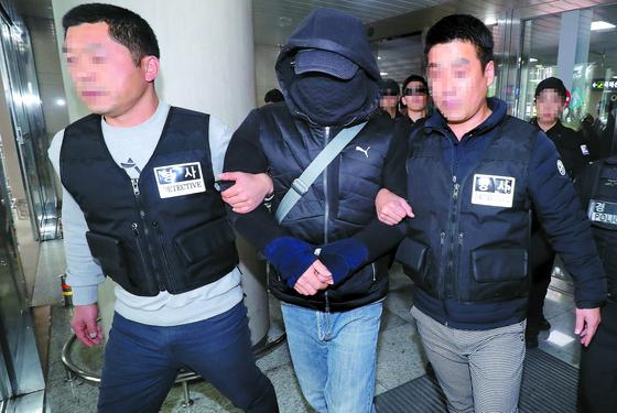 제주 보육교사 살인 사건의 범인으로 지목된 박모씨가 지난해 12월 대구에서 검거돼 제주국제공항을 통해 압송되고 있다. 그는 구속된 뒤 재판에 넘겨졌으나 지난 11일 1심 선고공판에서 무죄판결을 받고 석방됐다. [뉴스1]