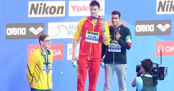 광주 남부대시립국제수영장에서 열린 2019 광주세계수영선수권대회 경영 남자 자유형 400m 결승 시상식에서 2위를 차지한 호주의 맥 호턴(왼쪽)이 도핑 논란에 휩싸인 1위 쑨양(가운데)을 의식한 듯 시상대에 함께 오르지 않은 채 뒷짐을 지고 있다. [뉴스1]