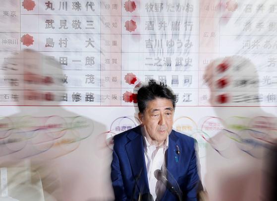아베 신조 일본 총리가 21일 자민당본부 개표센터에서 TV 중계를 보면서 참의원선거 결과를 확인하고 있다.[연합뉴스]