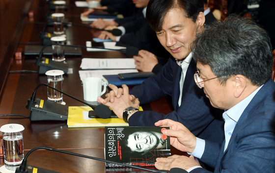 22일 청와대 여민관에서 열린 수석보좌관회의에서 강기정 정무수석(오른쪽)이 조국 민정수석이 가져온 책을 살펴보고 있다 . 청와대사진기자단