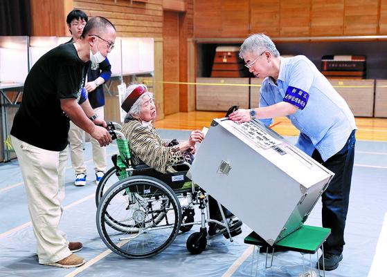 아베 신조 일본 총리의 중간평가 성격을 띠는 참의원 선거가 21일 실시됐다. 도쿄의 한 투표소에서 선관위 직원이 몸이 불편한 유권자를 위해 투표함을 기울여주고 있다. [EPA=연합뉴스]