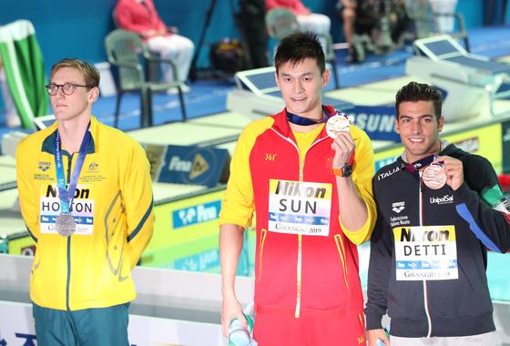 21일 2019 광주세계수영선수권대회 경영 남자 자유형 400m 결승에서 우승, 최초 4연패를 달성한 중국 쑨양이 금메달을 목에 걸고 포즈를 취하고 있다.   2위를 차지한 호주의 맥 호튼은 도핑 논란을 의식한 듯 시상대에 함께 오르지 않은 채 뒷짐을 지고 있다. [연합뉴스]