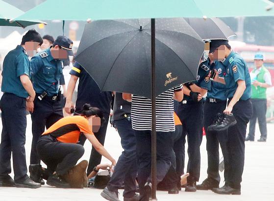 폭염 속 근무 중 이던 의무경찰이 구토와 어지럼증을 호소해 119 구급대원으로부터 응급조치를 받는 모습. 사진 속 인물들은 기사와 직접적인 관련이 없음. [연합뉴스]