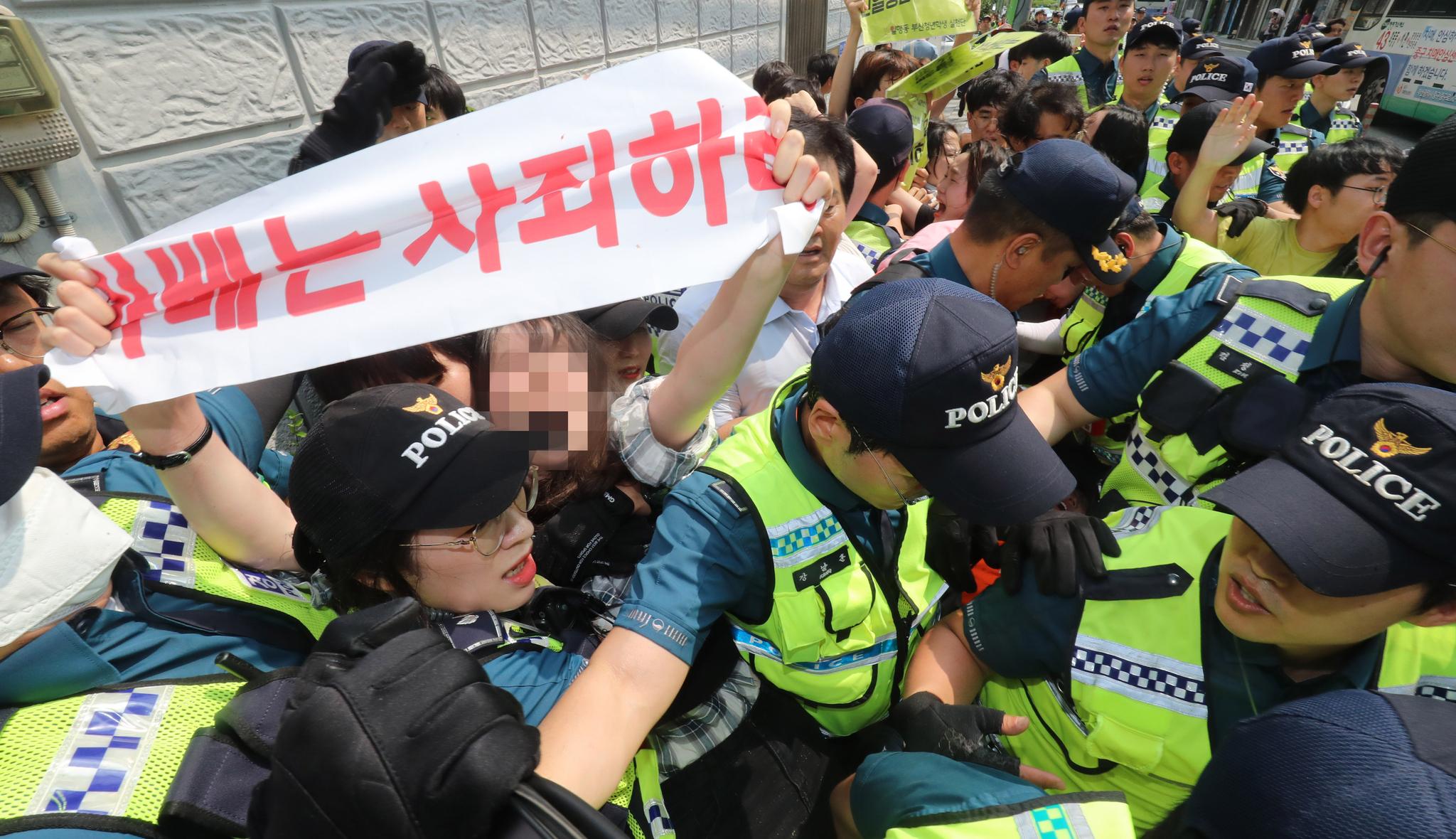 22일 오후 부산 동구 일본총영사관에 진입해 피켓 시위 등을 벌이던 반일부산청년학생실천단 소속 대학생 6명이 경찰에 연행되고 있다.송봉근 기자