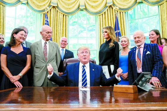 """도널드 트럼프 미국 대통령이 지난 19일(현지시간) 백악관에서 아폴로 11호에 탑승했던 마이클 콜린스(앞줄 왼쪽 둘째)와 버즈 올드린(앞줄 오른쪽) 등 우주인과 달 착륙 50주년 기념행사를 했다. 이 자리에서 트럼프 대통령은 기자단으로부터 한·일 갈등에 대한 질문을 받고 '사실은 한국 대통령이 내가 관여할 수 있는지 물어 왔다""""며 '아마도 (한·일 정상) 둘 다 원하면 나는 (관여)할 것""""이라고 부연 설명했다. [AP=연합뉴스]"""