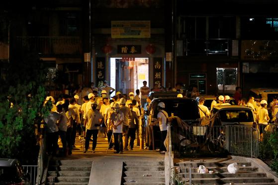 21일 밤 홍콩 지하철역의 흰 옷을 입은 남성들. 이들은 각목 등을 들고 역 입구를 에워싼 상태다.[로이터=연합뉴스]