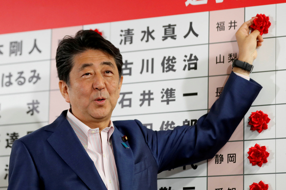 아베 신조 일본 총리가 21일 밤 자민당 본부에서 참의원 선거 당선자들의 이름 옆에 꽃을 달고 있다. [로이터=연합뉴스]
