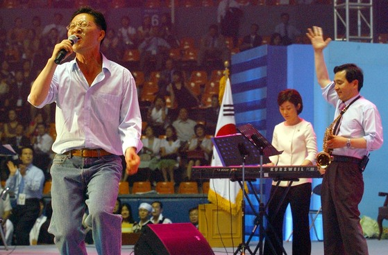 정두언은 노래를 좋아했다. 앨범을 4장 낸 가수다. 의원시절 지역에서 축사 대신 노래를 했다. 2004년 7월 한나라당(한국당의 전신) 전당대회에서 국회의원 밴드를 이끌며 노래하고 있다. [중앙포토]