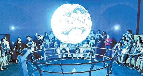 지난해 '달밤과학파티 19+' 행사에 참여한 참가자들이 천체 영상을 보며 설명을 듣고 있다. [사진 중앙DB]