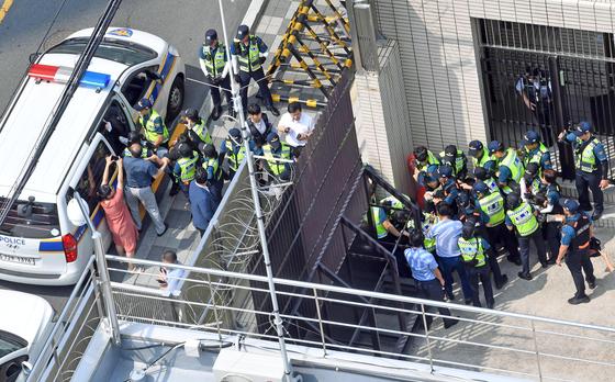 22일 오후 부산 동구 일본총영사관에서 대학생으로 추정되는 청년 6명이 영사관 안으로 들어가 피켓 시위 등을 벌이다 경찰에 연행되고 있다.[뉴시스]
