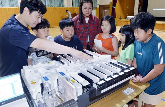 지난 22일 충남선관위가 마련한 '바다 건너 지금 만나러 갑니다. 찾아가는 민주주의 선거교실'에서 원산도 광명초등학교 학생들이 투표용지 분류기에 대한 설명을 듣고 있다. [프리랜서 김성태]