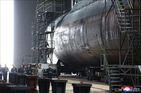 """김정은 북한 국무위원장이 새로 건조한 잠수함을 시찰했다고 조선중앙통신이 23일 보도했다. 통신은 ' 잠수함은 동해 작전 수역에서 임무를 수행하게 되며 작전 배치를 앞두고 있다""""고 밝혔으나 잠수함의 규모나 제원, 김 위원장의 방문 지역에 관해서는 언급하지 않았다. [조선중앙통신=연합뉴스]"""