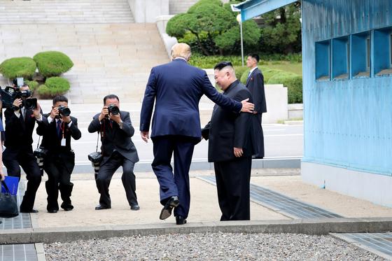 도널드 트럼프 미국 대통령이 지난달 30일 판문점 공동경비구역(JSA) 군사분계선 북측 지역에서 김정은 북한 국무위원장과 만나 군사분계선을 넘어 가고 있다. [청와대사진기자단]
