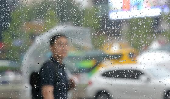 전국이 흐리고 장맛비가 내리는 25일 오전 서울 종로구 인근에서 한 시민이 우산을 쓰고 이동하고 있다. [연합뉴스]