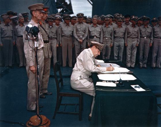 제2차 세계대전이 끝난뒤인 1945년 9월 2일 더글라스 맥아더 원수가 도쿄항에서 정박중인 미 태평양 함대 소속 미주리호 선상에서 일본으로부터 받아낸 항복문서에 서명하고 있다. [중앙포토]