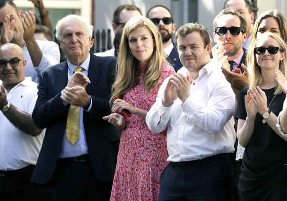 영국의 첫 '퍼스트 걸프렌드' 캐리 시먼즈(가운데)가 24일(현지시간) 총리관저 앞에서 존슨 총리의 첫 회견을 지켜보며 관저 직원들과 박수치고 있다. [AP=연합뉴스]