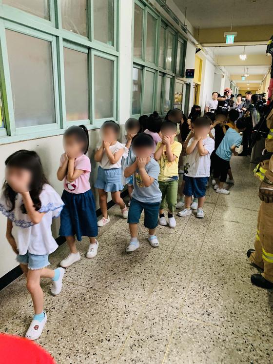 25일 오전 서울 구로구 구일초등학교에서 화학 용액 소량 유출 사고가 발생해 학생들이 대피하고 있다.  [구로소방서 제공]