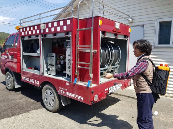 덤프트럭 운전사 김정오씨가 개인용 방진 펌프 매고 있다. 옆의 차량은 김씨가 운전한 옥계면 의용소방대 전용 소방차다. 편광현 기자
